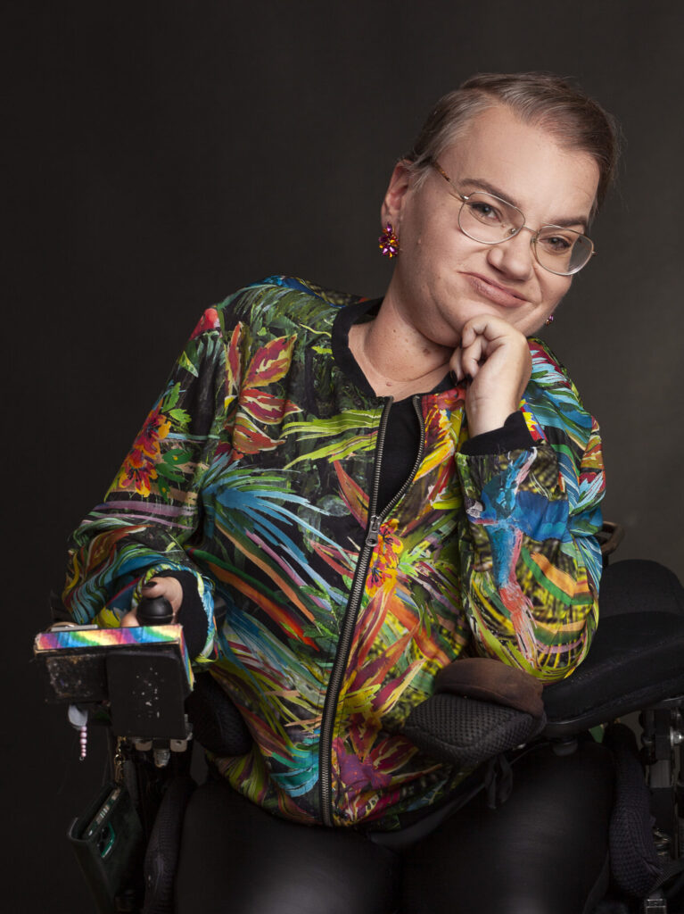 Woman with short, dark blonde hair wearing glasses, pink earrings, nude lipstick and a colorful, patterned jacket. She is looking straight at you and she is in an electric wheelchair.