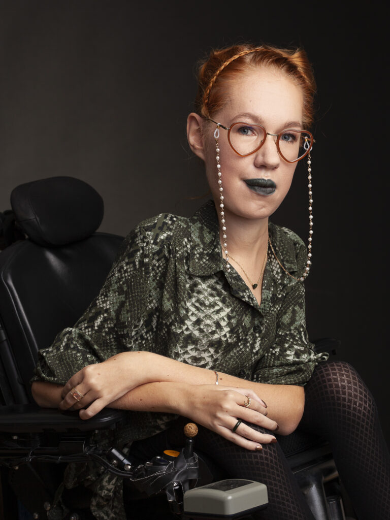 Woman with red braided hair in a bun wearing heart shaped glasses, glass chains with pearls, green lipstick, and a green, snakeskin patterned blouse. She is looking straight at you and she is in an electric wheelchair.